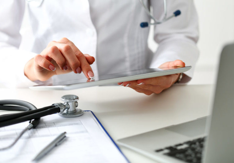 Female doctor hold digital tablet pc and point in touch screen with finger closeup.